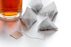 Чашка чаю с пакетиками чая на белой насмешке предпосылки вверх стоковые изображения