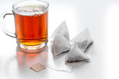 Чашка чаю с пакетиками чая на белой насмешке предпосылки вверх стоковое изображение