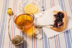 Чашка чаю с стрейнером чая на ткани таблицы Стоковое Изображение