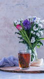 Чашка чаю с тимианом и букетом цветков на предпосылке против детенышей весны цветка принципиальной схемы предпосылки белых желтых Стоковые Фотографии RF