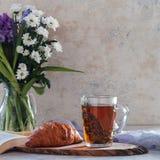 Чашка чаю с тимианом и букетом цветков на предпосылке против детенышей весны цветка принципиальной схемы предпосылки белых желтых Стоковые Изображения