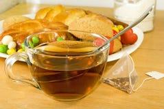 Чашка чаю, торты и плюшки на таблице Стоковые Фото