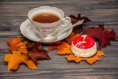 Чашка чаю, торт и листья на деревянной предпосылке стоковое изображение rf
