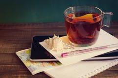 Чашка чаю, cockleshell моря, таблетка, карточка, ручка, туристская карта и тетрадь Стоковая Фотография