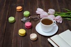 Чашка чаю, macarons, стекла, розовые тюльпаны и тетрадь на woode стоковые фото