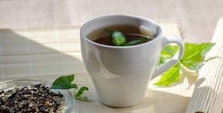 Чашка чая мяты и пук мяты на таблице Стоковые Изображения