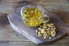 Чашка чая стоцвета с сухим стоцветом на деревянной доске стоковое фото