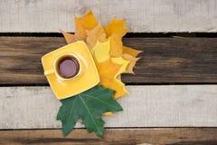 Чашка чая с листьями осени на деревянном столе Стоковые Изображения