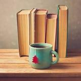 Чашка чая с рождественской елкой и старыми книгами над предпосылкой нерезкости Стоковые Изображения