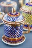 Чашка чая 5 цветов тайского изящного искусства традиционная (Bencharong) над голубой расплывчатой предпосылкой Стоковое Изображение RF
