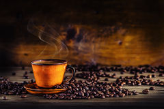 Чашка черного кофе и разлитых кофейных зерен помадка чашки круасанта кофе пролома предпосылки Стоковое Изображение