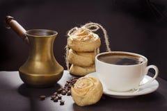 Чашка черного кофе и старого медного cezve и с печеньями на черном блюде шифера помадка чашки круасанта кофе пролома предпосылки Стоковая Фотография