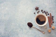 Чашка черного кофе, кофейных зерен, желтого сахарного песка и циннамона Стоковое Изображение