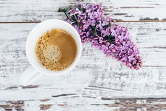 Чашка черного кофе на винтажном деревянном столе с ветвью взгляд сверху сирени Стоковые Изображения RF