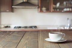 Чашка черного кофе на деревянной столешнице в запачканной современной кухне конец вверх крыто стоковые фотографии rf
