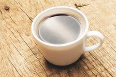 Чашка черного кофе на старом деревянном столе - съемке студии Фильтрованное изображение: влияние обрабатываемое крестом винтажное Стоковое Фото