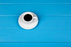 Чашка черного питья на голубой деревянной предпосылке Стоковые Изображения