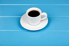 Чашка черного питья на голубой деревянной предпосылке Стоковая Фотография RF