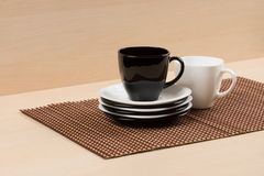 Чашка черного чая на стоге белых и черных плит приближает к белой чашке чая на tablemat Стоковые Фотографии RF