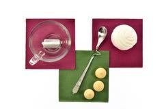 Чашка черного чая с зефирами и печеньями ложки на покрашенных бумажных салфетках Стоковая Фотография RF