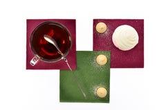 Чашка черного чая с зефирами и печеньями ложки на покрашенных бумажных салфетках Стоковые Фотографии RF