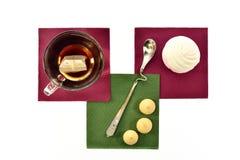 Чашка черного чая с зефирами и печеньями ложки на покрашенных бумажных салфетках Стоковые Изображения