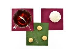 Чашка черного чая с зефирами и печеньями ложки на покрашенных бумажных салфетках Стоковое Изображение