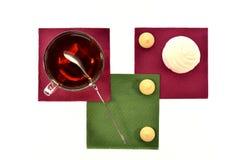 Чашка черного чая с зефирами и печеньями ложки на покрашенных бумажных салфетках Стоковое фото RF