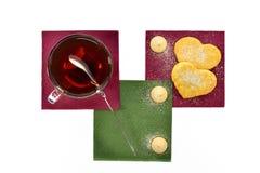 Чашка черного чая с зефирами и печеньями ложки на покрашенных бумажных салфетках Стоковое Фото