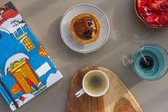 Чашка эспрессо на деревянной предпосылке и тортов с гайками и клубниками на поддоннике на серой предпосылке и свече Стоковая Фотография