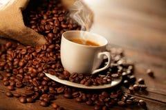 Чашка эспрессо с сумкой джута и кофейными зернами стоковое изображение