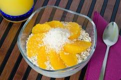 Чашка югурта с свежим muesli апельсина и кокоса Стоковое фото RF