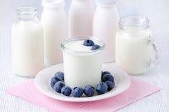 Чашка югурта с blueberrys и различными бутылками питья югурта и молока на таблице Стоковое Изображение RF