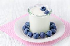 Чашка югурта с blueberrys на таблице Стоковые Изображения