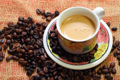 Чашка latte coffe стоя на кофейных зернах Стоковые Изображения
