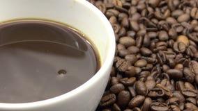 чашка 4k a черного кофе над зажаренными в духовке кофейными зернами сток-видео