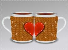2 чашки в свитере украшенном с сердцами Стоковые Изображения