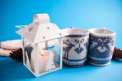 Чашки горячего питья одели в связанных случаях рождества на голубой предпосылке Стоковое Фото