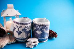 Чашки горячего питья одели в связанных случаях рождества на голубой предпосылке Стоковая Фотография RF