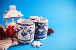Чашки горячего питья одели в связанных случаях рождества на голубой предпосылке Стоковые Фото