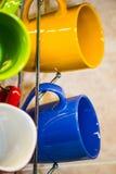Чашки и кружки вися на holde Стоковая Фотография RF