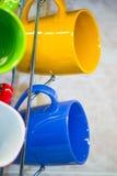 Чашки и кружки вися на holde Стоковое Фото