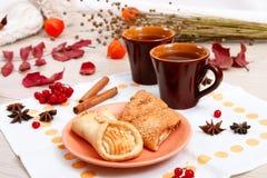 2 чашки коричневой глины с чаем на белой салфетке белья Печенья масла с вареньем и тортом плода с творогом на r стоковые изображения