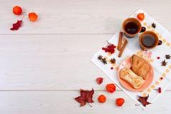 2 чашки коричневой глины с чаем на белой салфетке белья Печенья масла с вареньем и тортом плода с творогом на r стоковые фото