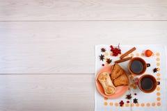 2 чашки коричневой глины с чаем на белой салфетке белья Печенья масла с вареньем и тортом плода с творогом на r стоковое изображение