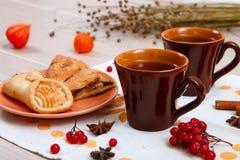 2 чашки коричневой глины с чаем на белой салфетке белья Печенья масла с вареньем и тортом плода с творогом на r стоковое фото