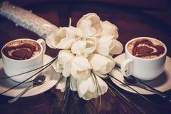 2 чашки кофе и белых тюльпаны Стоковая Фотография