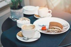 2 чашки кофе и тирамису на черной предпосылке таблицы с красивым сердцем искусства latte сформировали стоковая фотография