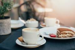 2 чашки кофе и тирамису на черной предпосылке таблицы с красивым сердцем искусства latte сформировали стоковые изображения rf