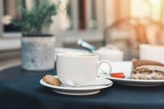 2 чашки кофе и тирамису на черной предпосылке таблицы с красивым сердцем искусства latte сформировали стоковые фотографии rf